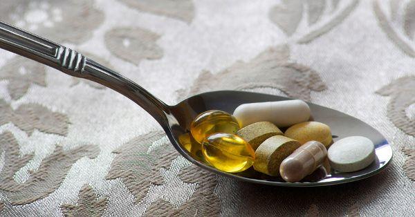Nahrungsergänzungsmittel: Kapseln und Dragees auf einem Löffel